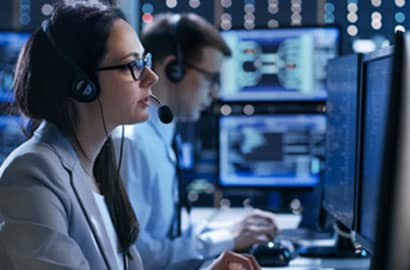 Two dispatchers sit and work in a 911 call center, answering emergency calls and processing information on their computers.
