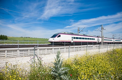 A modern passenger train flashes across the landscape.
