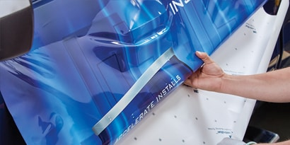 A man installing a blue and white 3M IJ180mC print wrap film on the side of a truck, showing the ease of application and liner release.