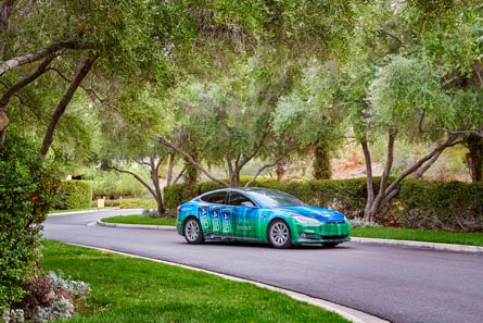 Small sedan parked in a suburban neighborhood wrapped in green and blue 3M™ Envision™ Print Wrap Film.