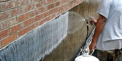 Worker spraying 3M™ HoldFast 70 Spray Adhesive on a below-grade wall before attaching waterproofing or insulation