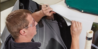 A man applying a black 3M IJ180mc print wrap film on the side of a white car.