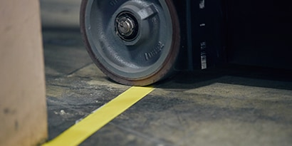 Closeup image of a vehicle wheel crossing a taped yellow lane marking