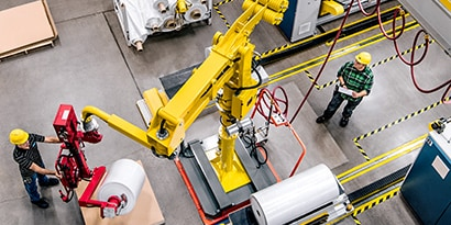 Overhead image of a worker operating a machine while another stands in an area marked off with black-and-yellow stripe tape
