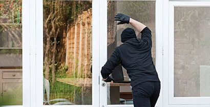 A person dressed in all black tries to look into a home he might want to rob through a window with reflective, security-enhancing window films.