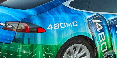 A close up of the back right side of a sedan wrapped in a blue and green 3m envision print wrap LX480mC & SV480mC film.