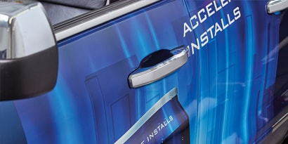A close up of a blue car's driver side door and handle, wrapped in 3M IJ180mC-10 print wrap film.