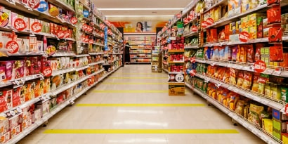 Image of a grocery aisle marked with strips of yellow tape to aid social distancing