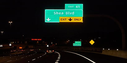 Highway signs are highly reflective over a dark road at nighttime.