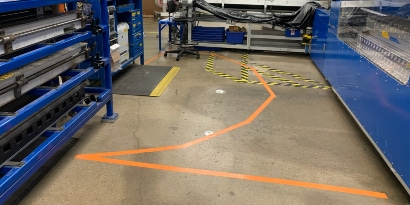 Image of a factory floor with orange tape marking an arc around a standing mat at a workstation