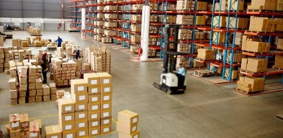 Warehouse with piles of boxes on floors and shelves