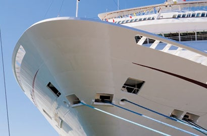 The bow and superstructure of a sleek white cruise ship.