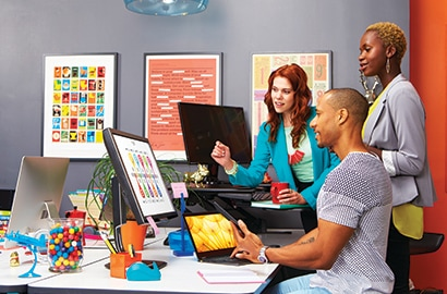Three people looking at a desktop computer's screen.