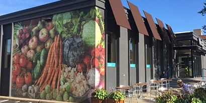 Exterior of grocery store with a 3M printable film wall graphic of fresh vegetables