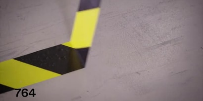 Video still of 3M™ General Purpose Vinyl Tape 764 yellow-and-black stripe tape being pulled up cleanly