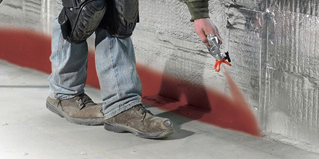Worker spraying a firestop product along a wall-floor joint
