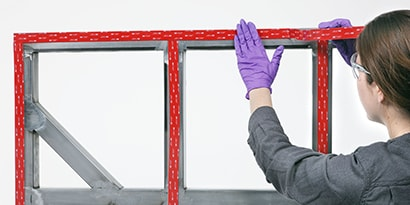 Technician applies industrial adhesive tape to a panel to frame assembly
