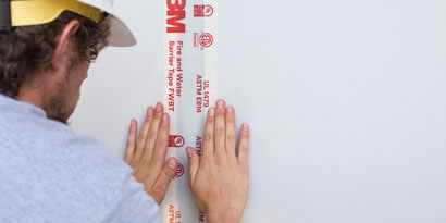 Person applying 3m VHB tape to wall
