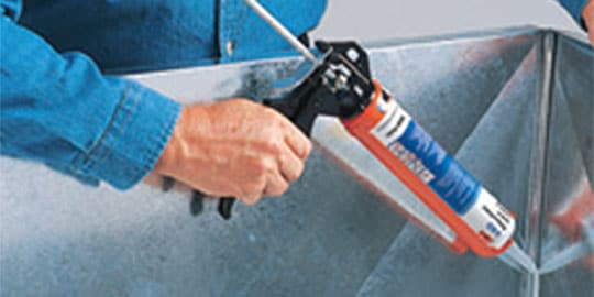 Adhesive or sealant being applied over seam in metal sheet
