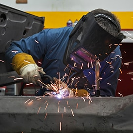 Sparks fly as technician welds metal substrates together in a factory