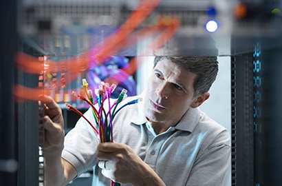 A technician performs repairs on a server in a data center.
