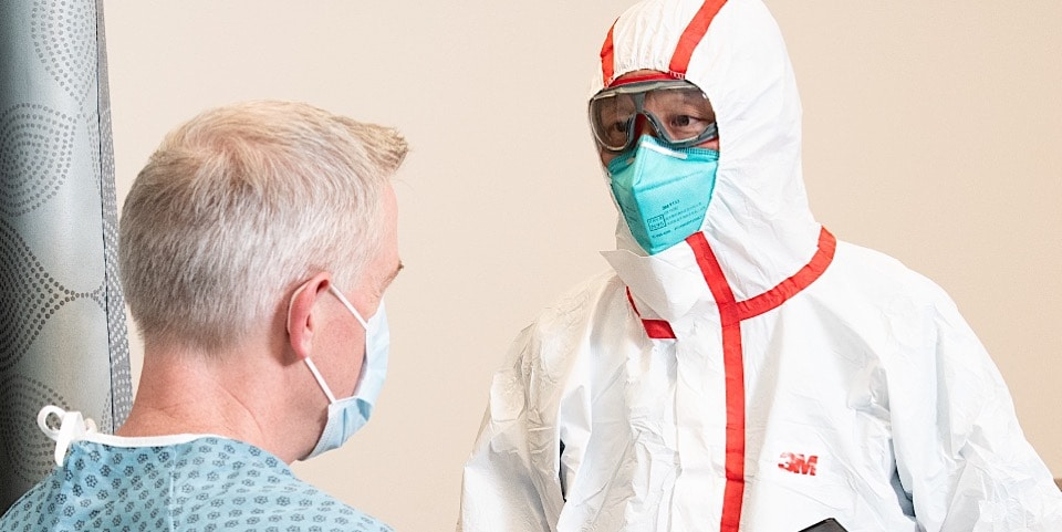 health care provider wearing full body suit, a particulate respirator and eye goggles talking with patient in mask