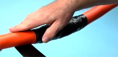 A man applies black 3M tape to repair an electrical cable jacket.