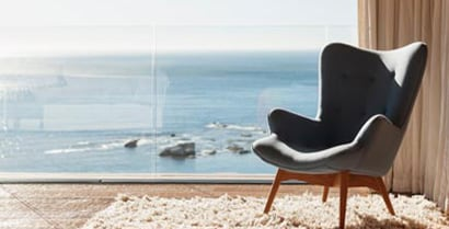 A special chair is placed in front of floor to ceiling windows that look out at the ocean.