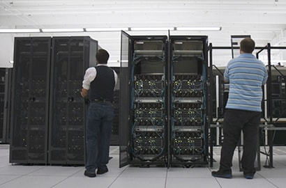 Two men work among the densely packed server racks of a modern supercomputer.