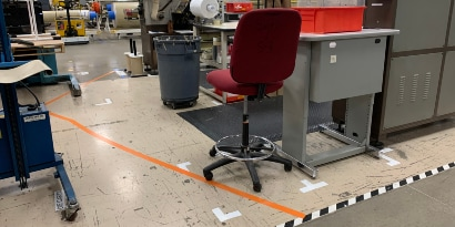 Image of a floor with orange tape marking separation between workstations and black and white stripe tape marking a walkway