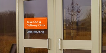 "Image of a double door with a sign saying ""Take Out & Delivery Only"""