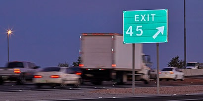 Vehicles speed past a reflective exit sign on the highway.