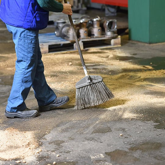 Person sweeping inside of a facility