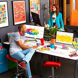 An image of two people in anoffice setting with bright and colorful desktop display monitors.